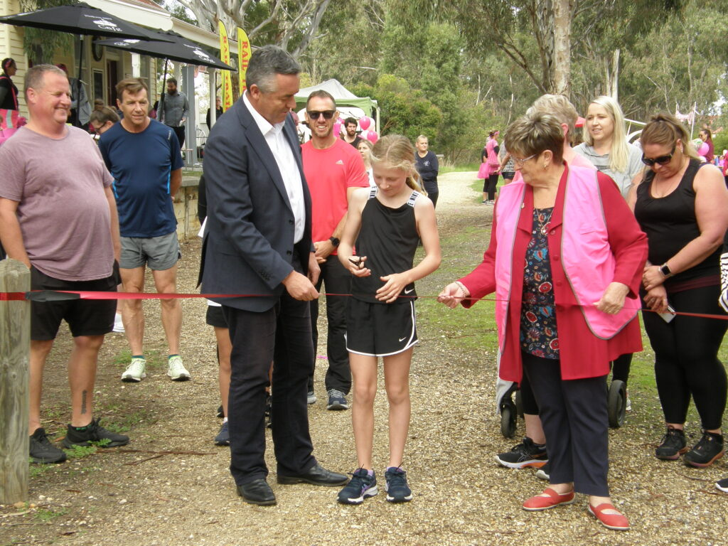Young girl cuts ribbon alongside The Hon Darren Chester and Helen Hoppner, Chairperson of Gippsland Plains Rail Trail